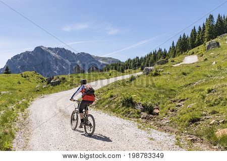 Mountainbiker on a gravel road on Nassfeld in Carnic Alps with view to mountain Rosskofel