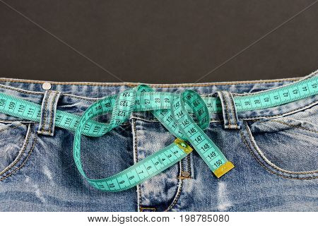 Healthy lifestyle and dieting concept. Jeans and measure tape around waist close up. Jeans with blue measure tape belt with copy space. Top part of denim trousers isolated on black background.