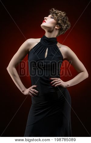beautiful young woman dancer in tango dress on red background. copy space.
