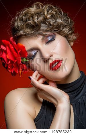 beautiful young woman dancer in tango dress with rose in hair on red background. copy space.