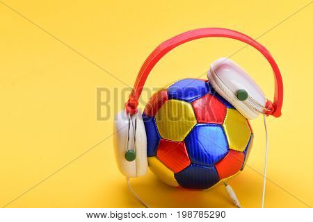 Modern earphones and football isolated on light orange background. Headset for music placed on ball. Headphones in white and red color with colorful soccer ball. Music and sports equipment concept