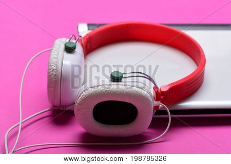 Headphones And Silver Laptop. Electronics Isolated On Magenta Pink Background