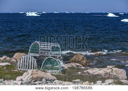 lobster traps, rocky Newfoundland coast with icebergs