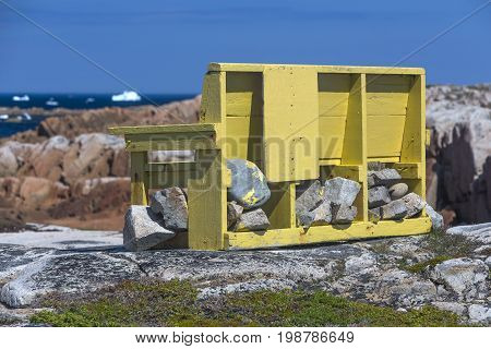 wood bench weighted down with rocks, Newfoundland