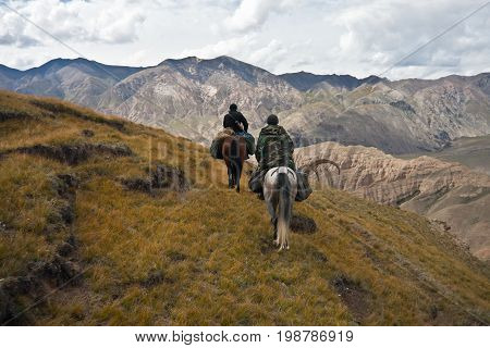 Hunters two horses returned with a trophy after a hunt in the mountains of Tien Shan Kyrgyzstan