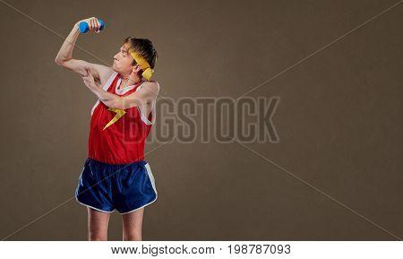 A funny, thin freak guy in sportswear with dumbbells showing little muscles.