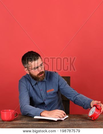 Man With Beard And Glasses Holds Alarm Clock And Notebook