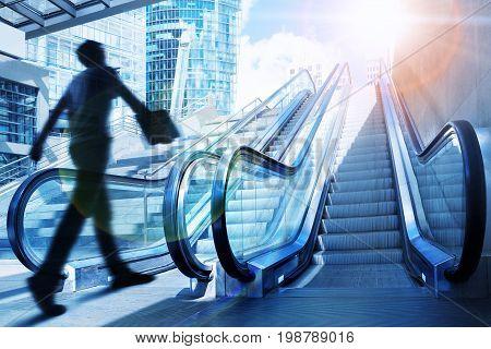 modern escalators against a sunny blue sky