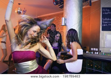 a group of young people are dancing in a nightclub.