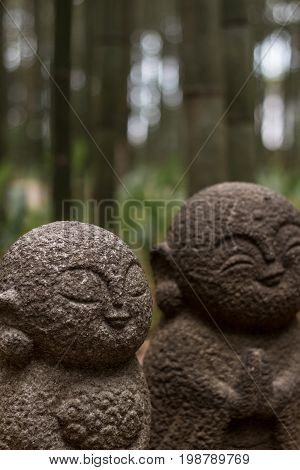 Two stone shinto buddhist statues amongst bamboo forest in Kyoto, Japan