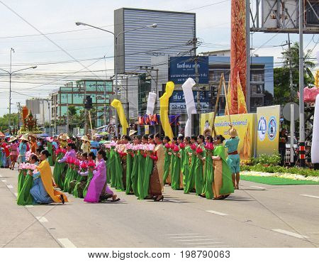 SUPHANBURI THAILAND - July 9 2017 : The parade of young women indigenous costumes at the candlelight parade Traditional of Buddhism July 9 2017 SUPHANBURI THAILAND