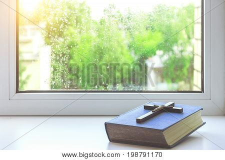 The bible and the old wooden cross on the windowsill. Rain drops on the glass. Rainy evening. The light from the window. Church utensils.