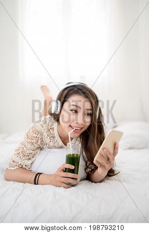 Woman Relaxing in bed and listening to music relaxing in her living room