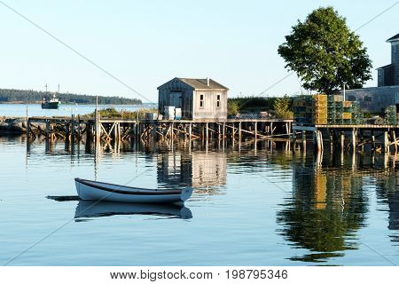 A scenic view of Bass Harbor in Bernard Maine. A reflection of a pier extending into the harbor with lobster traps and a boat house. A row boat is in the forground and a fishing boat is in the background.