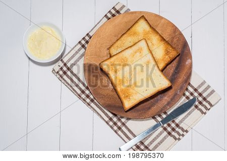 Close-up of slice of toast bread with butter on wood table