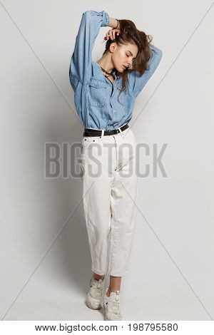 Full length portrait of happy young woman posing in jean shirt and white jeans on against white background