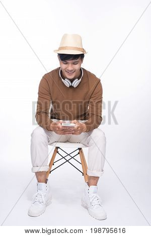 Smart casual asian man seated on chair, holding smartphone in studio background
