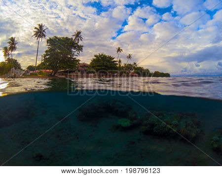 Split photo with tropical island and underwater coral reef. Double landscape with sea and sky. Above and below waterline in tropical seashore. Sunset on beach. Exotic island shore view. Split seascape
