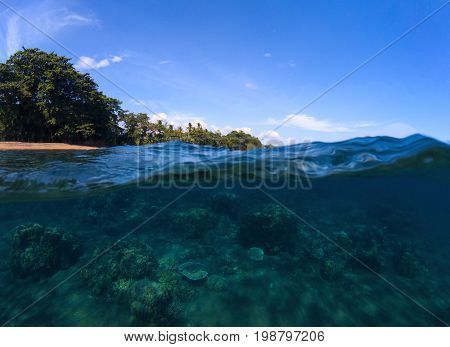 Double landscape with sea and sky. Sea panorama split photo. Undersea view of tropical island seashore. Above and below sea waterline. Blue seawater with coral reef. Exotic island seaside vacation