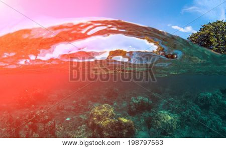 Double landscape with sea and sky. Split photo of sunny seashore. Above and below sea waterline. Tropical island nature. Seascape split view. Hot sun flare over sea water. Clear sea wave look through