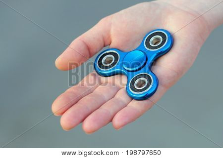 Blue metal popular fidget spinner toy on the palm of your hand take it