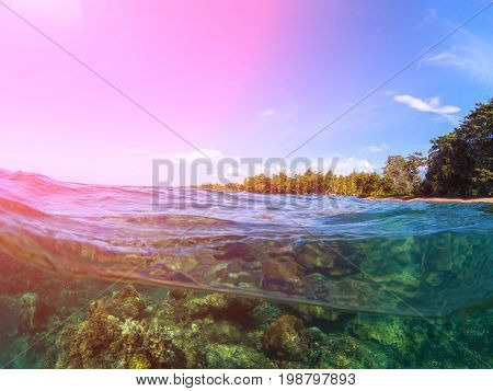 Double landscape with sea and sky. Sea panorama split photo. Tropical island lagoon. Underwater coral reef. Above and below waterline sea view. Exotic seashore. Sunshine on sea. Pink flare on seascape
