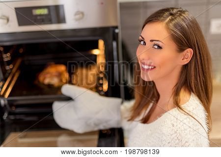 Beautiful young woman preparing meat in oven in the domestic kitchen. Looking at camera. Selective focus.