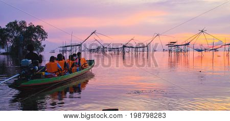 Silhouette of traditional fishing method using a bamboo square dip net .Traveller on the boat and see the sunrise at Pak Pra lakePattalungThailand. Twilght skyorange skyred skypurple sky background.