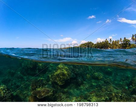 Double landscape with sea and sky. Split photo with tropical island and underwater coral reef. Above and below sea waterline. Exotic seashore panorama. Split seascape of tropical island lagoon in sun