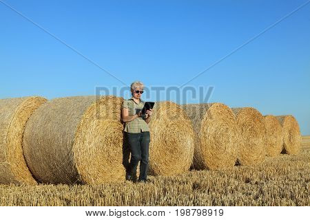 Farmer And Bale Of Straw In Field