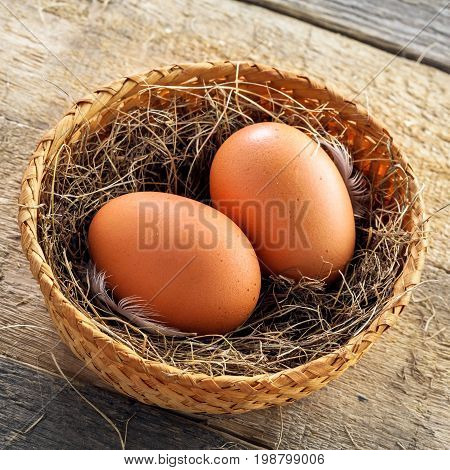Couple of fresh chicken eggs in a rural basket with hey and feather on a wooden background. Close-up shot. Top view.