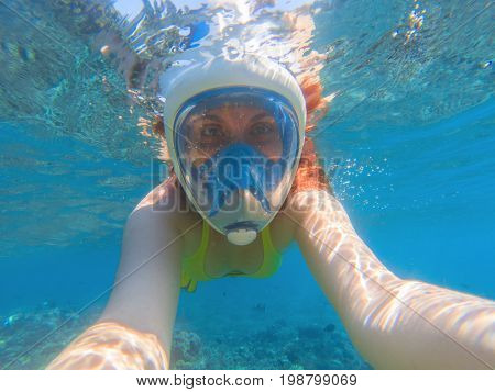 Snorkeling girl underwater selfie. Snorkeling in full face mask. Summer activity. Beautiful girl in shallow seawater. Underwater photo of diving person. Active vacation by seaside. Water sport image