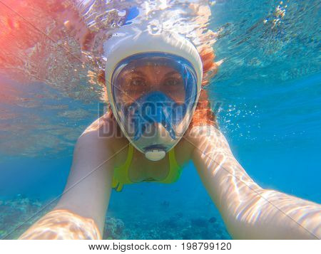 Snorkel girl underwater selfie. Snorkeling in full face mask. Summer activity. Beautiful girl in sea water. Underwater photo of diving person. Active vacation by seaside. Water sport in tropical sea.