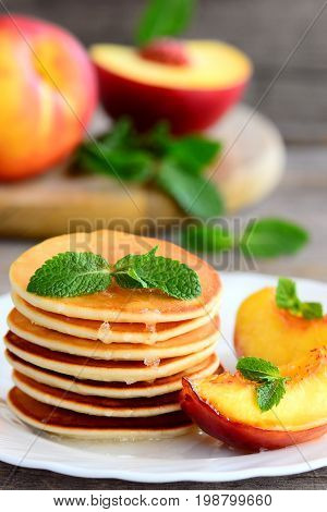 Tasty pancakes with syrup and grilled nectarines on a white plate. Home sweet pancake recipe. Summer breakfast or brunch for children and the whole family. Vertical photo