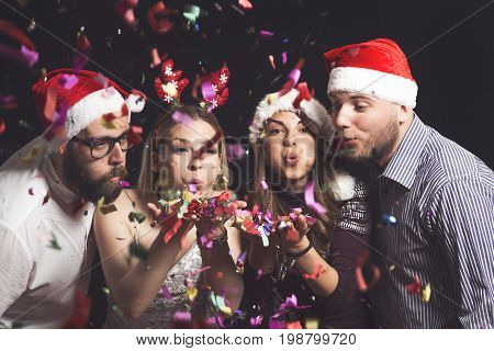 Two beautiful young couples wearing Santa's hats blowing colorful confetti at midnight at New Year's Eve party