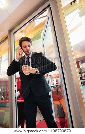 stressed businessman getting his early-morning coffee at a cafe and hurrying out the door to get to his next appointment