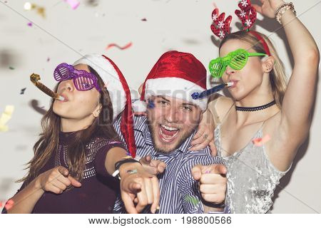 Group of young friends dancing making funny faces blowing party whistles and having fun at New Year's Eve party