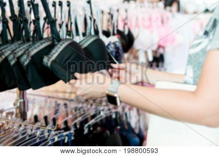 Blurry Background of Teen girl choose a bra in black.