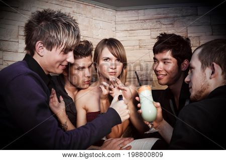 a pretty young woman is surrounded by four men trying to seduce her.
