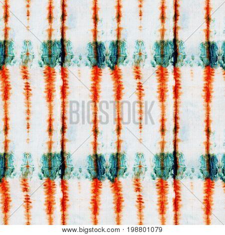 Seamless tie-dye pattern of orange and green color on white silk. Hand painting fabrics - nodular batik. Shibori dyeing.