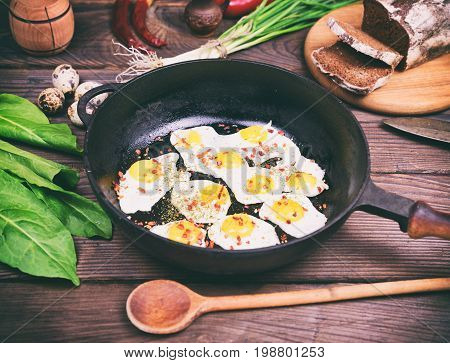 Fried eggs with quail eggs in a black frying pan on a brown wooden background