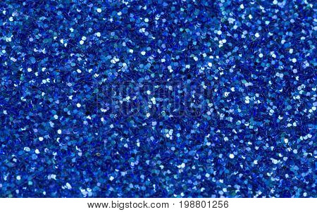 Blue abstract background. Blue glitter closeup photo.Night sky shimmer wrapping paper. Sparkling glitter festive backgrop. Glamour greeting card or wedding invitation template. Real glitter macrophoto