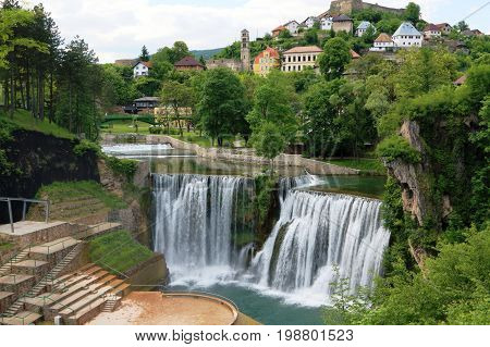 Pliva Waterfall in Jajce in Bosnia and Herzegovina with water rushing down the 20m height cliff with the old town in the background