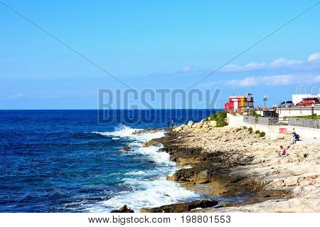 BUGIBBA, MALTA - MARCH 28, 2017 - Tourists relaxing on the rocky shoreline Bugibba Malta Europe, March 28, 2017.