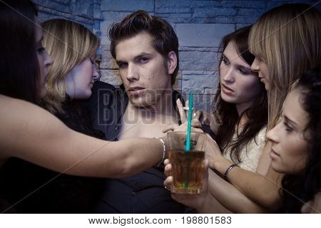 a pretty young man is surrounded by several women trying to seduce him.
