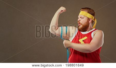A funny fat freak man in sports clothes measures his arm with a centimeter.