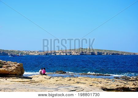BUGIBBA, MALTA - MARCH 28, 2017 - A couple sitting on the rocky shoreline with views across the bay Bugibba Malta Europe, March 28, 2017.