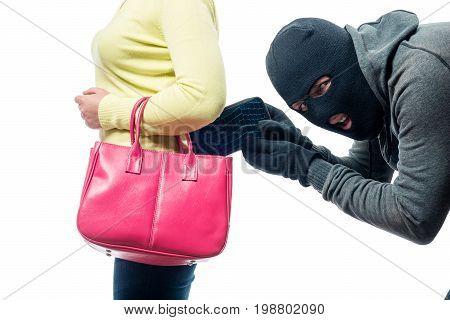 A thief pickpocket steals a purse from a women's bag in a balaclava