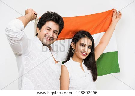 Portrait of indian happy young couple in ethnic wear holding Indian flag. Asian handsome young man and woman and indian tricolour or flag. Standing isolated over white background