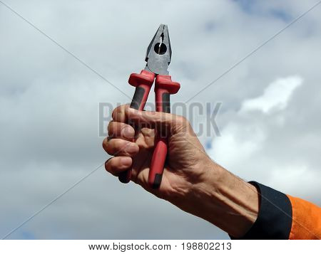 Hand holds universal pliers against the sky. Hand tools.